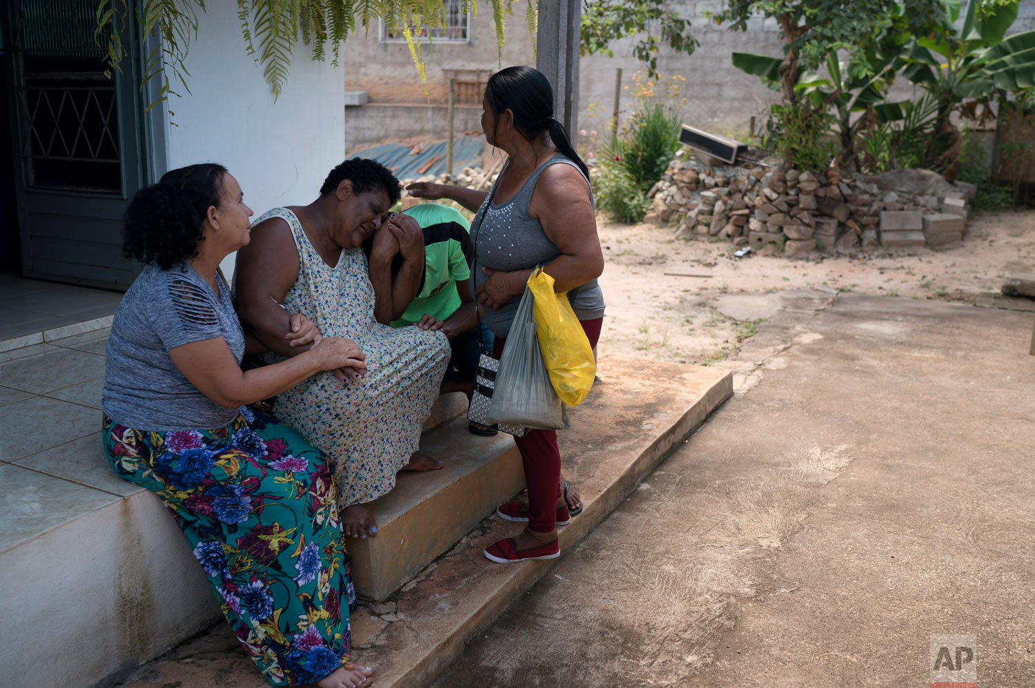 Malvina Firmina Nunes and her son Fernando are comforted by friends at their home as they grieve for their missing 35-year-old son and brother, Peterson, after a deadly Vale dam collapse in Brumadinho, Brazil, Jan. 30, 2019. (AP Photo/Leo Correa)