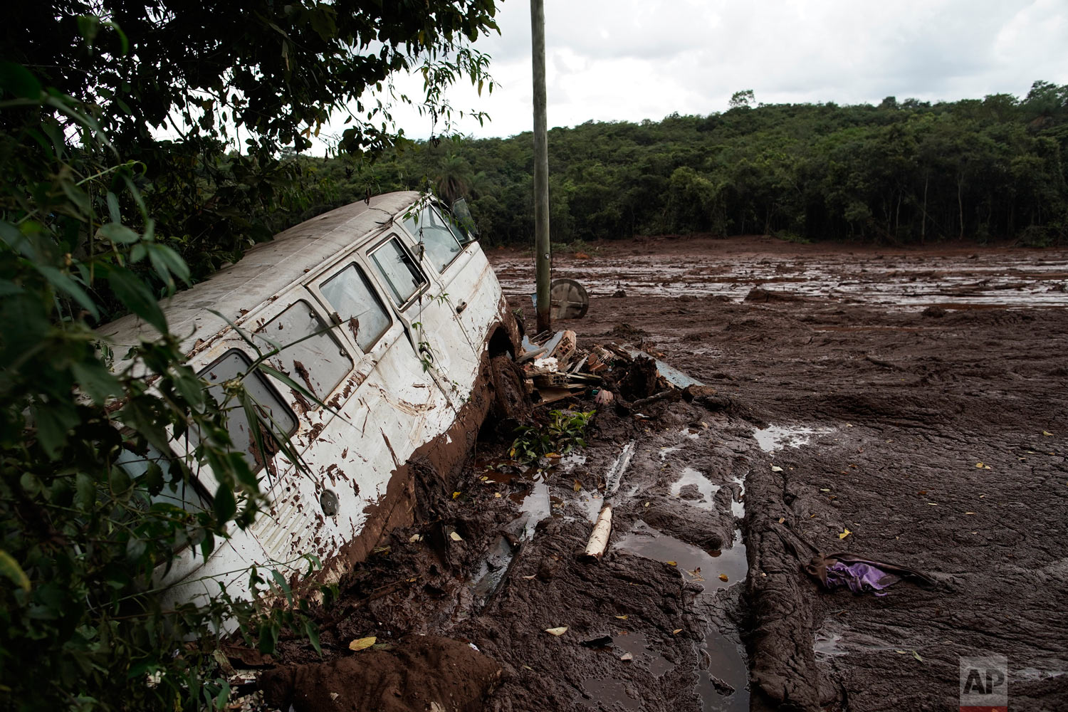 A van is half submerged in the mud after a Vale dam collapsed near Brumadinho, Brazil, Jan. 26, 2019. (AP Photo/Leo Correa)