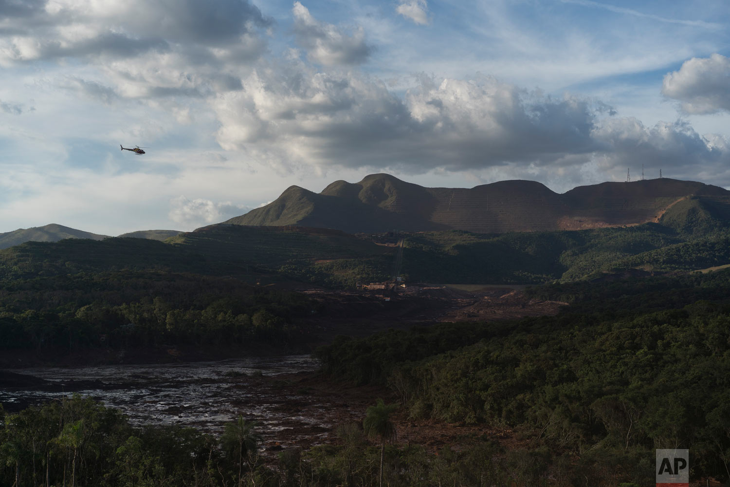Members of the rescue operation fly over the site where a Vale dam collapsed two days prior in Brumadinho, Brazil, Jan. 27, 2019. (AP Photo/Leo Correa)