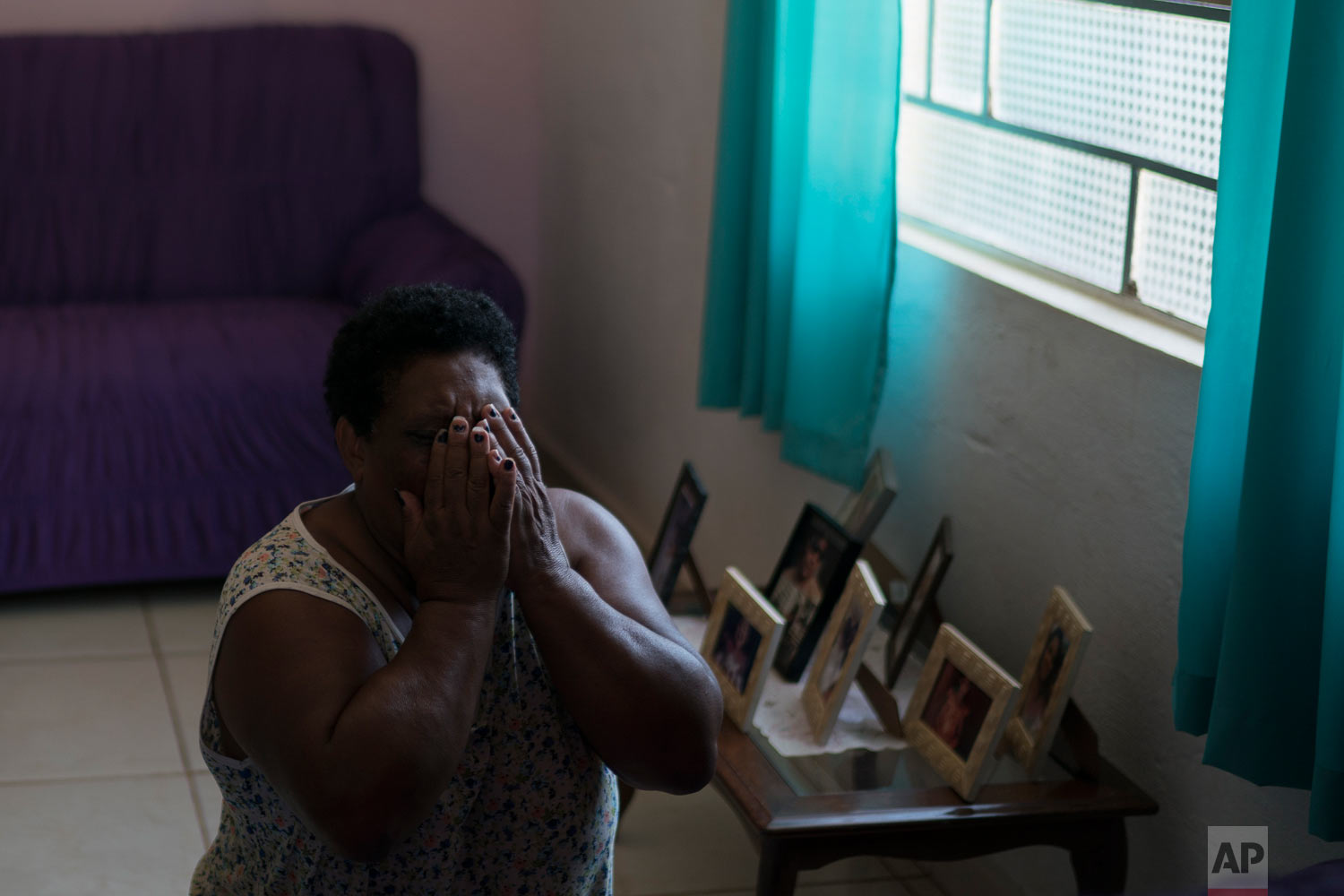 Malvina Firmina Nunes prays on her knees at home in Brumadinho, Brazil, Jan. 30, 2019, while one of her four adult children remains missing following a Vale dam collapsed. (AP Photo/Leo Correa)