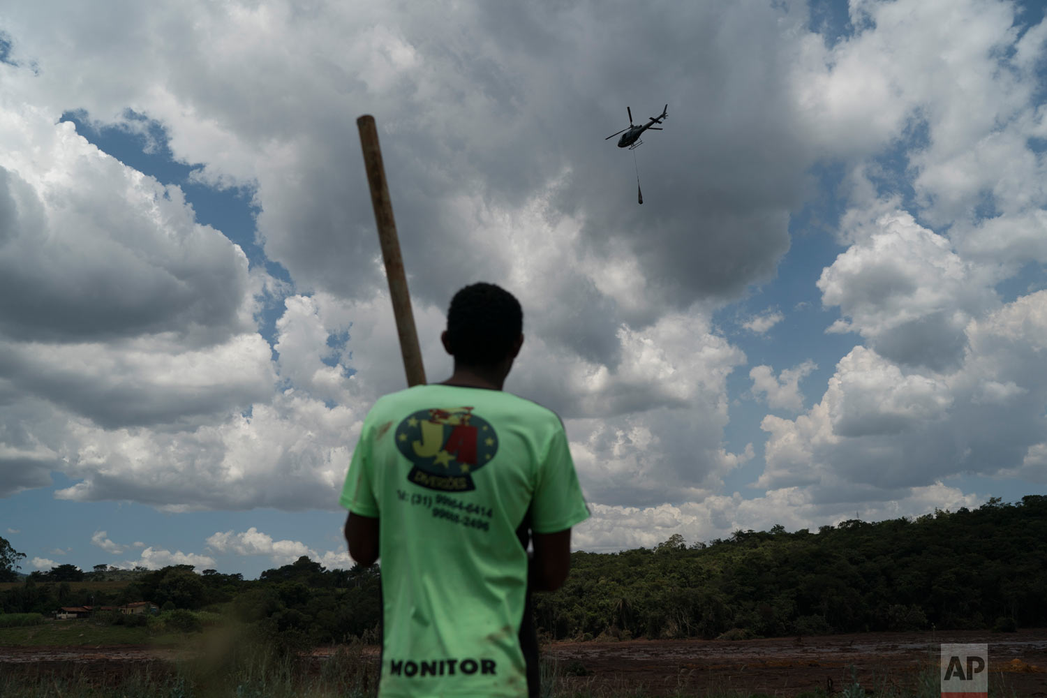 Fernando Nunes watches a helicopter carry a body away from the mud after a Vale dam collapse while his brother Peterson, a Vale employee, remains missing in Brumadinho, Brazil, Jan. 30, 2019, two days before his body was found. (AP Photo/Leo Correa)