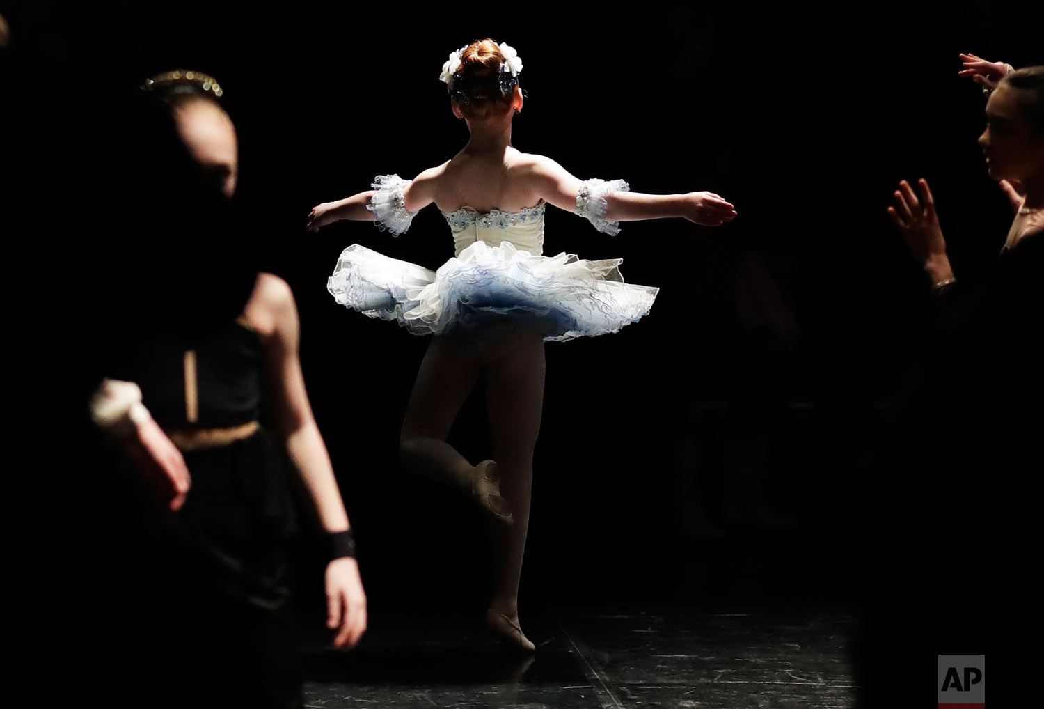 Fallon Tewell, center, and other young dancers warm up for the Youth America Grand Prix North America regional semi-finals in River Forest, Ill. (AP Photo/Nam Y. Huh)