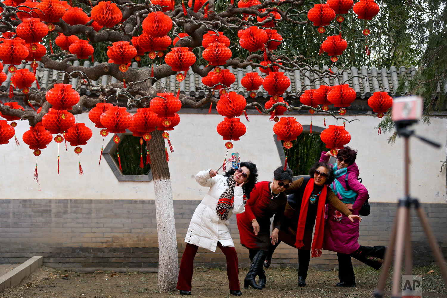 Women take a selfie near a tree decorated with red lanterns ahead of the Lunar New Year at Ditan Park in Beijing, Wednesday, Jan. 30, 2019. (AP Photo/Andy Wong)