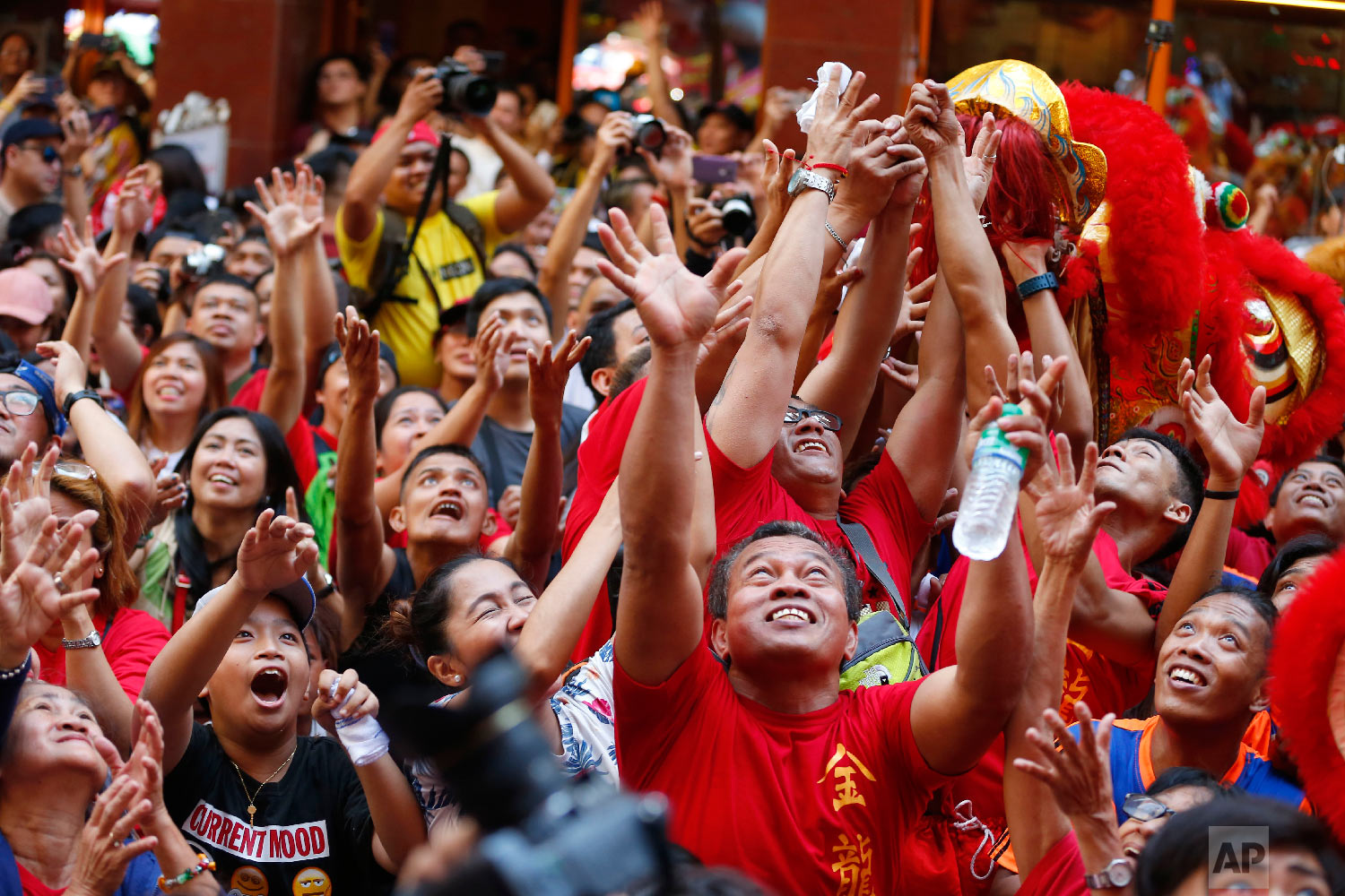 Crowds jostle to grab festive items being thrown at them during celebrations of the Lunar New Year in the Chinatown district in Manila, Philippines, Tuesday, Feb. 5, 2019. (AP Photo/Bullit Marquez)