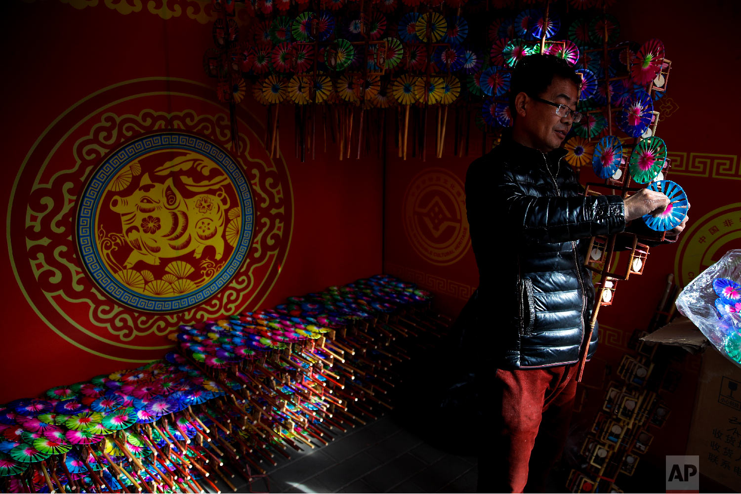 A vendor adds a wooden windmill toy to his store at the Longtan Park for a temple fair ahead of Chinese Lunar New Year in Beijing, Sunday, Feb. 3, 2019. (AP Photo/Andy Wong)