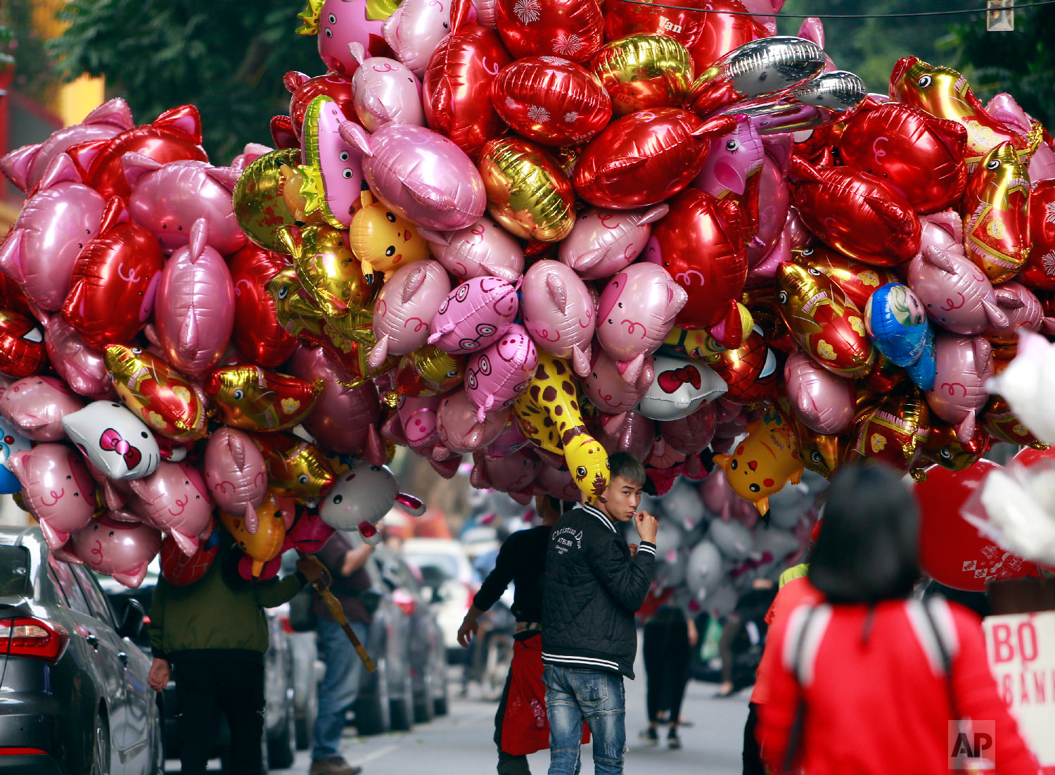 Vendors carrying pig-shaped balloons for sale to mark the Lunar New Year in Hanoi, Vietnam, Sunday, Feb. 3, 2019. (AP Photo/Hau Dinh)