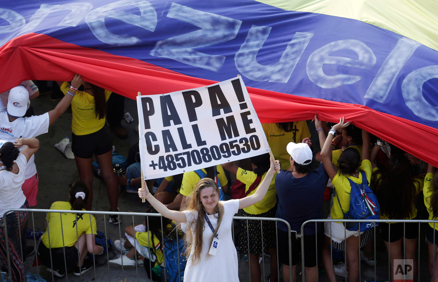 A young woman holds a sign asking Pope Francis to call her as she waits for him to arrive for an outdoor Mass in Panama City, Jan. 24, 2019. (AP Photo/Arnulfo Franco)