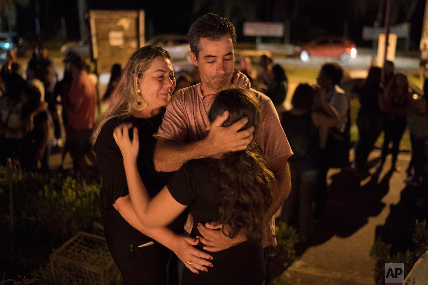A family embraces during a vigil for the victims of the collapsed mining dam in Brumadinho, Brazil, Jan. 29, 2019. (AP Photo/Leo Correa)