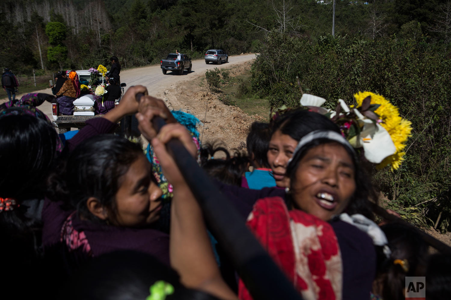 Women travel in the back of a truck during the funeral procession for Felipe Gomez Alonzo to the cemetery in Yalambojoch, Guatemala, Jan. 27, 2019. On Christmas Eve, the 8-year-old boy became the second Guatemalan child to die while in U.S. custody near the Mexican border. (AP Photo/Oliver de Ros)