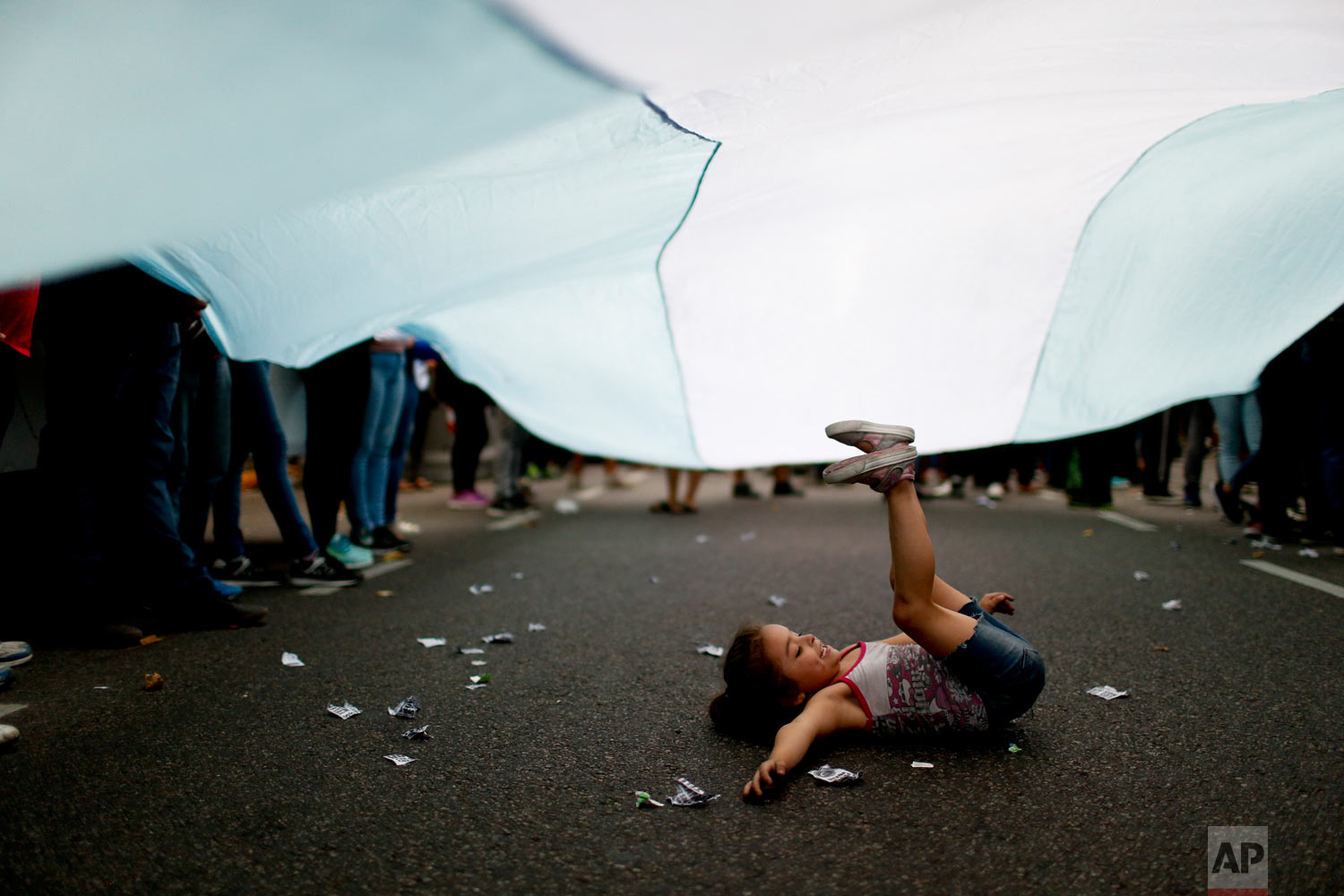 A girl plays under an Argentine flag as demonstrators protest the increase in public service fees in Buenos Aires, Argentina, Jan. 10, 2019. (AP Photo/Natacha Pisarenko)