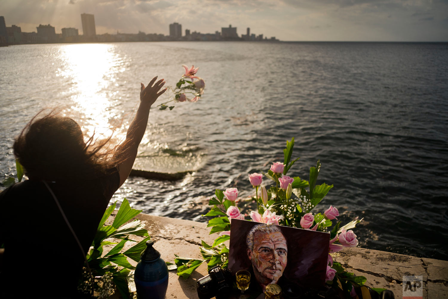 A woman throws flowers into the sea during a memorial service for late photojournalist Desmond Boylan, from the Malecon promenade where some of his ashes were also scattered into the water at sunset in Havana, Cuba, Jan. 1, 2019. Boylan, a photographer who covered war and conflict across the world before dedicating his life to documenting the daily joys and tribulations of life in Cuba for The Associated Press, died suddenly while on assignment on Dec. 29 in Havana. He was 54. (AP Photo/Ramon Espinosa)