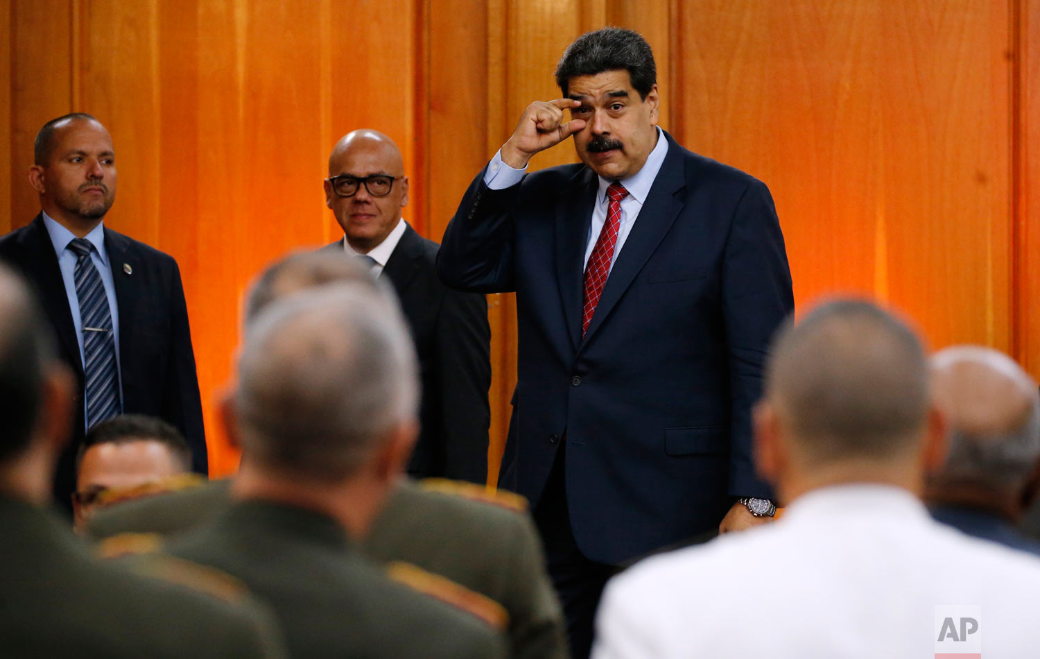 Venezuelan President Nicolas Maduro gestures to military leaders to keep their eyes open, after an opposition leader declared himself interim president, as he leaves a press conference at Miraflores presidential palace in Caracas, Venezuela, Jan. 25, 2019. (AP Photo/Ariana Cubillos)
