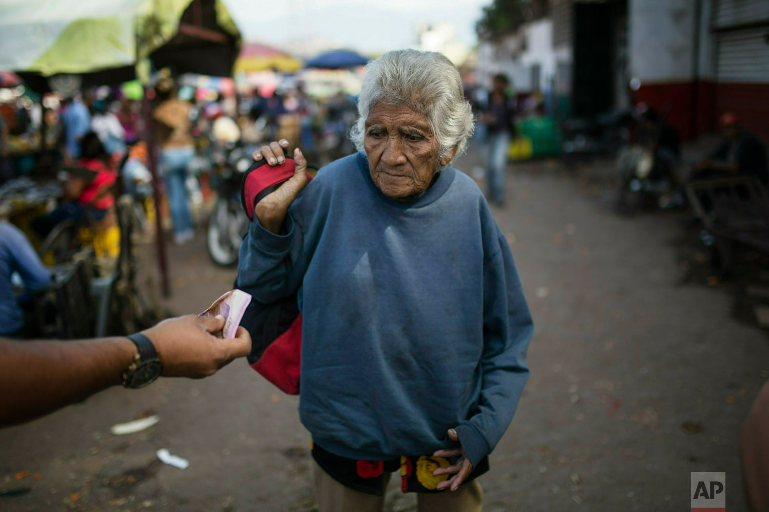 An elderly woman is offered cash as she begs at a wholesale food market in Caracas, Venezuela, Jan. 28, 2019. Economists agree that the longer the standoff between a U.S.-backed opposition leader and the president drags on, the more regular Venezuelans are likely to suffer. (AP Photo/Rodrigo Abd)