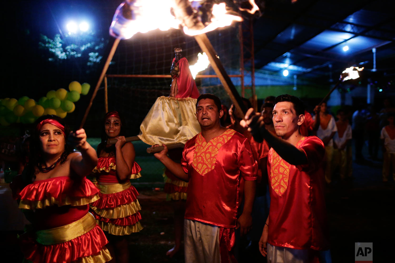 Adolfo Bogarin, president of the Afro-Paraguayan cultural group Kamba Cua, center, helps carry a statue of Saint Balthazar, one of the Three Kings, as they hold a torch-lit procession to mark Epiphany in Fernando de la Mora, Paraguay, Jan. 5, 2019. (AP Photo/Jorge Saenz)
