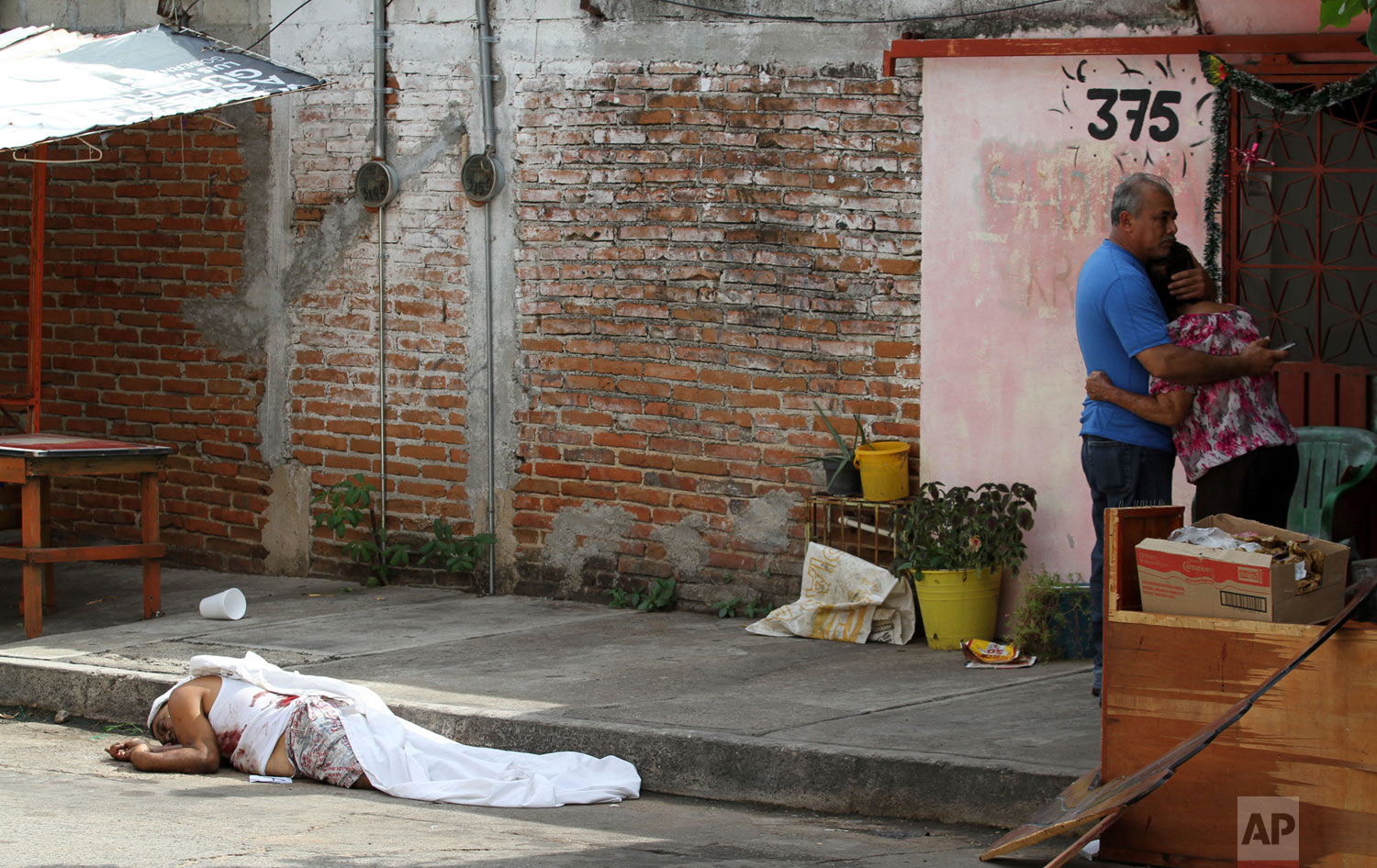 A man's body lies on the pavement after he was shot to death, as his parents hug nearby in Acapulco, Mexico, Jan. 2, 2019. (AP Photo/Bernardindo Hernandez)