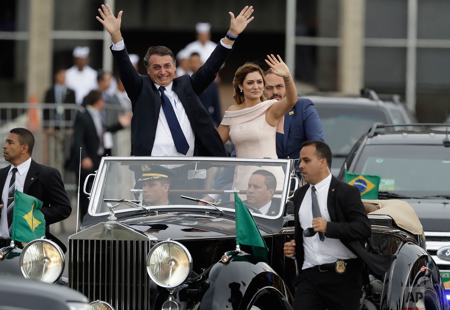 Flanked by first lady Michelle Bolsonaro, Brazil's President Jair Bolsonaro, waves after his swearing-in ceremony in Brasilia, Brazil, Jan. 1, 2019. (AP Photo/Andre Penner)