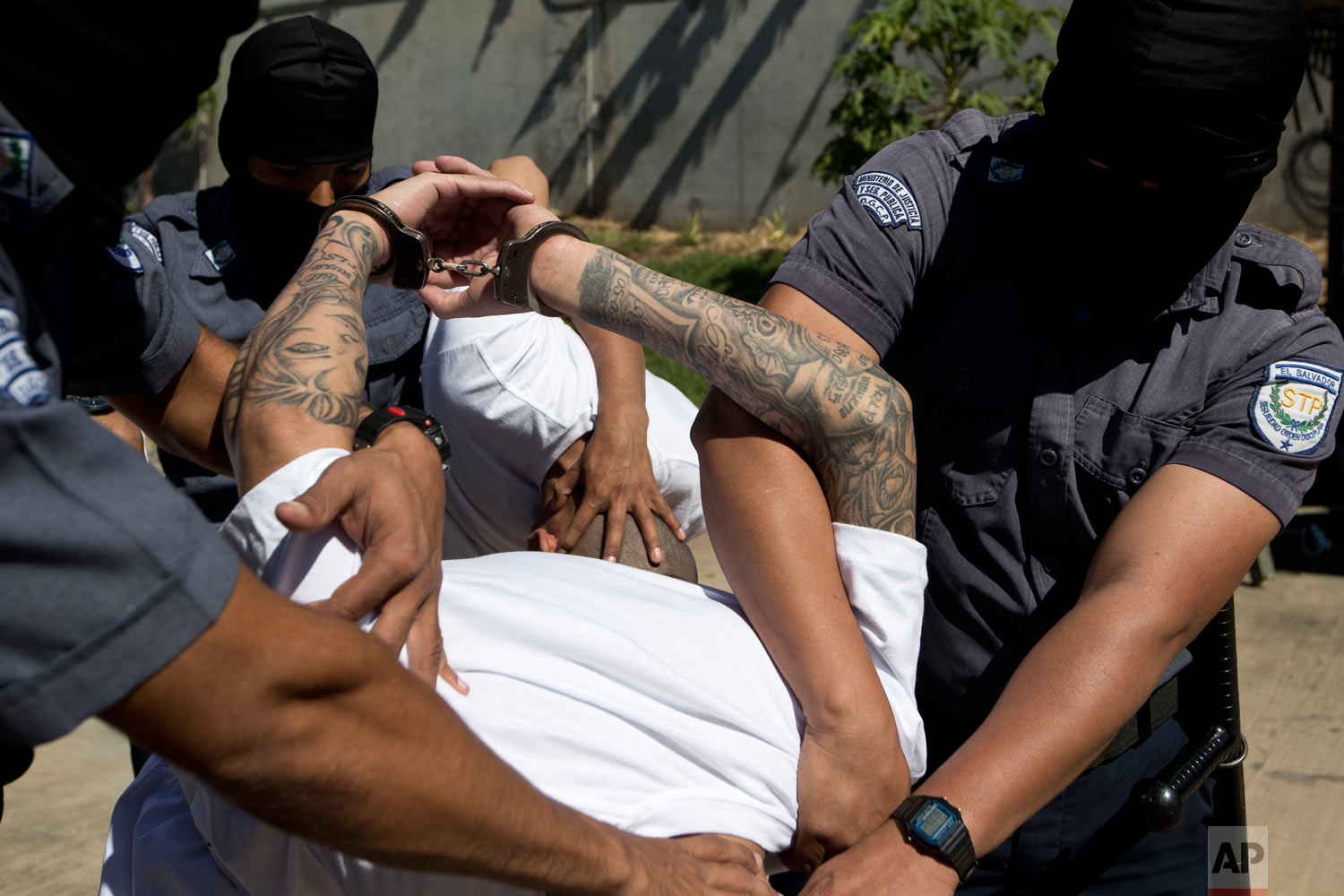 Jailed men identified by authorities as members of the Mara Salvatrucha gang are escorted in handcuffs by masked prison guards to the Zacatras high security prison where they will await trials for murder in Zacatecoluca, El Salvador, Jan. 31, 2019. (AP Photo/Moises Castillo)