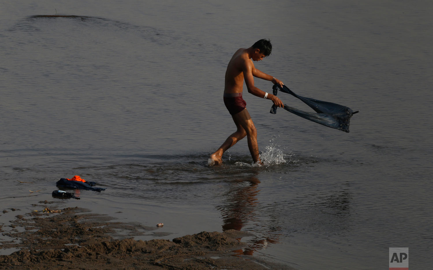 A Central American migrant awaiting a humanitarian visa from Mexico washes his pants in the Suchiate River, the natural the border between Mexico and Guatemala, on the riverbank near Ciudad Hidalgo, Chiapas state, Mexico, Jan. 20, 2019. (AP Photo/Marco Ugarte)