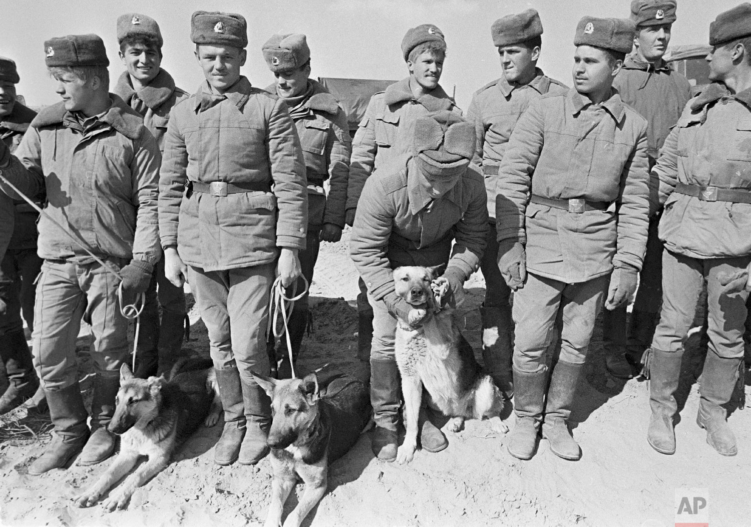 Soviet Army soldiers with their war-dogs line up after their unit crossed a bridge on the border between Afghanistan and then Soviet Uzbekistan near the Uzbek town of Termez, Uzbekistan on Feb. 15, 1989. (AP Photo/Alexander Zemlianichenko)