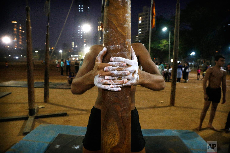 A player tightens his grip on a mallakhamb pole as he trains at Shivaji Park on Feb. 4, 2019, in Mumbai, India. (AP Photo/Rafiq Maqbool)
