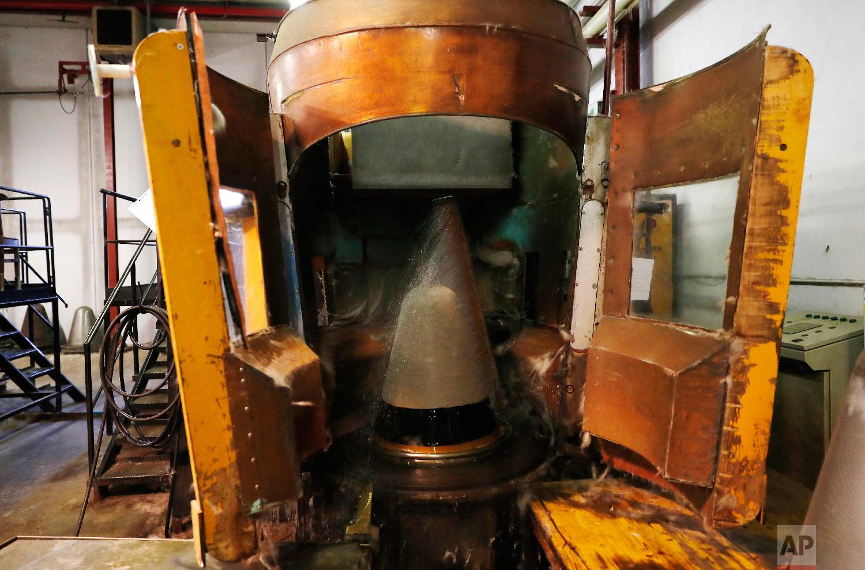 A machine uses water to shape a fur hat in Borsalino's fur factory, in Spinetta Marengo, near Alessandria, Italy, Thursday, Jan. 17, 2019. (AP Photo/Antonio Calanni)