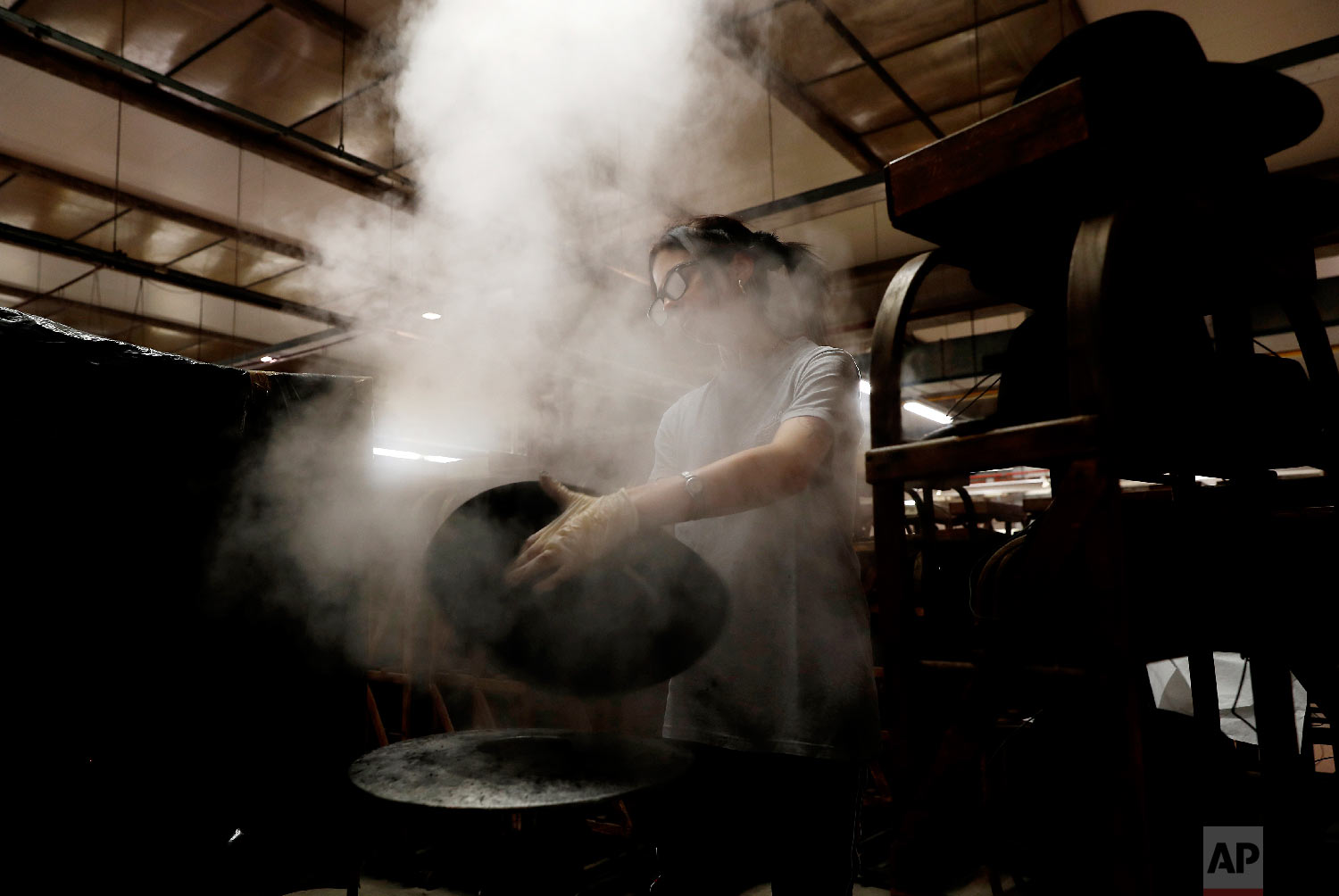 Steam is used to mould a fur hat in Borsalino's hat factory, in Spinetta Marengo, near Alessandria, Italy, Thursday, Jan. 17, 2019. (AP Photo/Antonio Calanni)