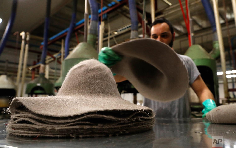 A man piles felt hats inside Borsalino's hat factory, in Spinetta Marengo, near Alessandria, Italy, Thursday, Jan. 17, 2019. (AP Photo/Antonio Calanni)