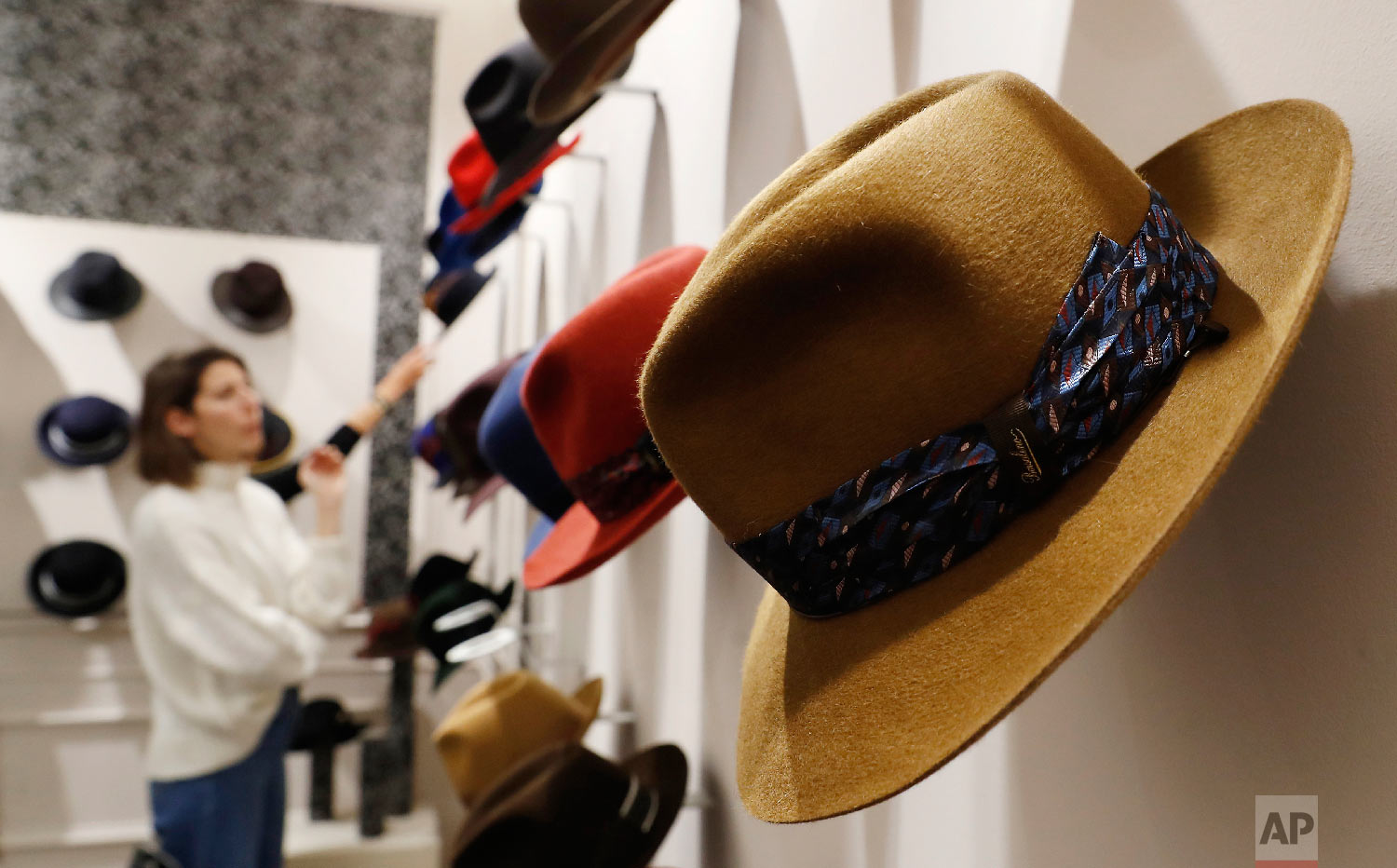 A woman looks at hats in a Borsalino store in downtown Milan, Italy, Wednesday, Jan. 16, 2019. (AP Photo/Antonio Calanni)
