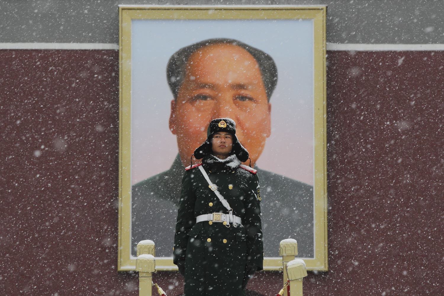 A paramilitary police officer stands guard under the portrait of former leader Mao Zedong outside Tiananmen Gate as snow falls in Beijing, Tuesday, Feb. 12, 2019. China's capital is mostly dry in the winter but a storm system brought snow to the city on Tuesday morning. (AP Photo/Andy Wong)