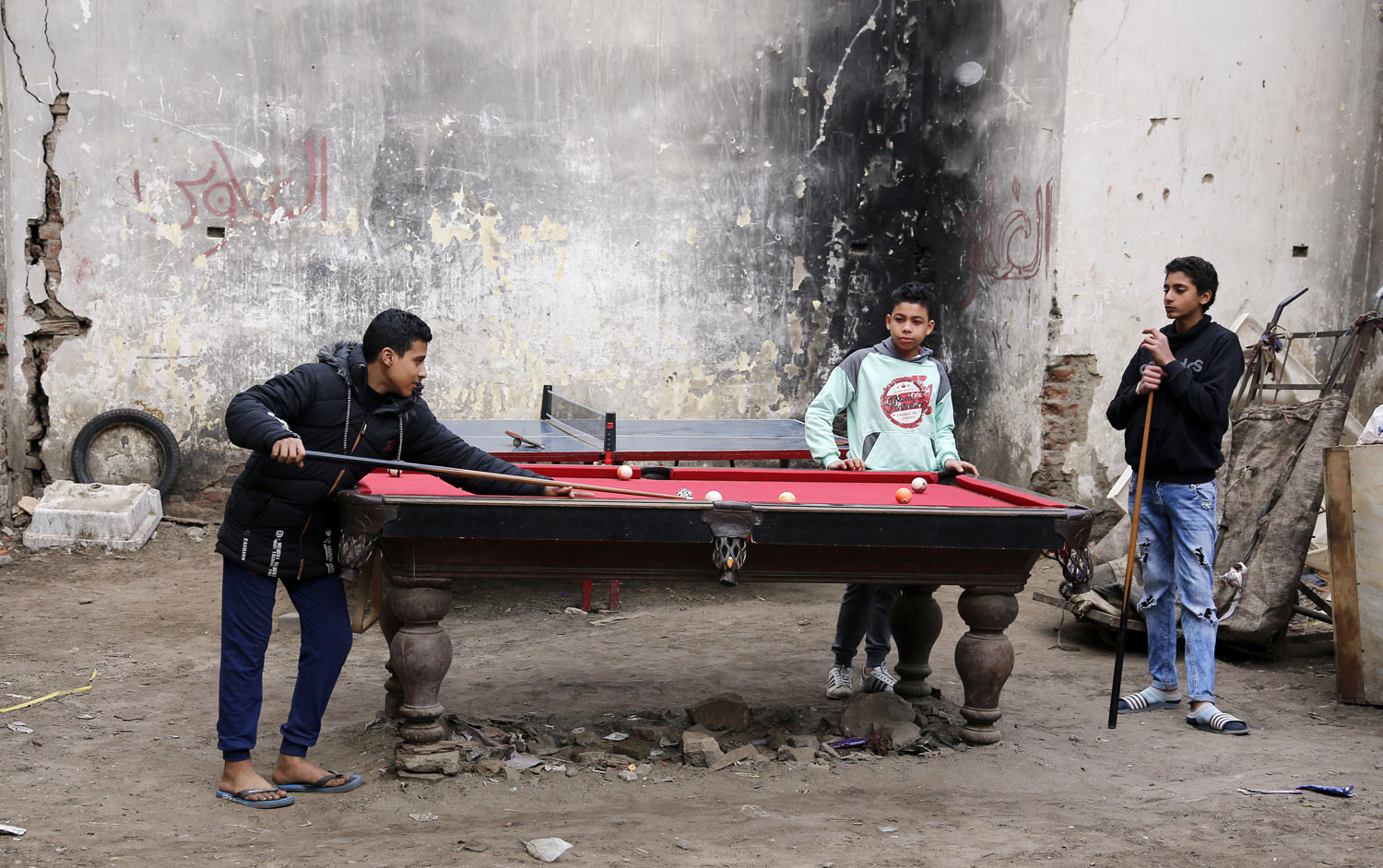 Boys play billiards as they rent a table for 4 Egyptian Pounds (U.S. $0.25), at Darb Shughlan, a popular district in Cairo, Egypt, on Friday, Feb. 15, 2019. (AP Photo/Amr Nabil)