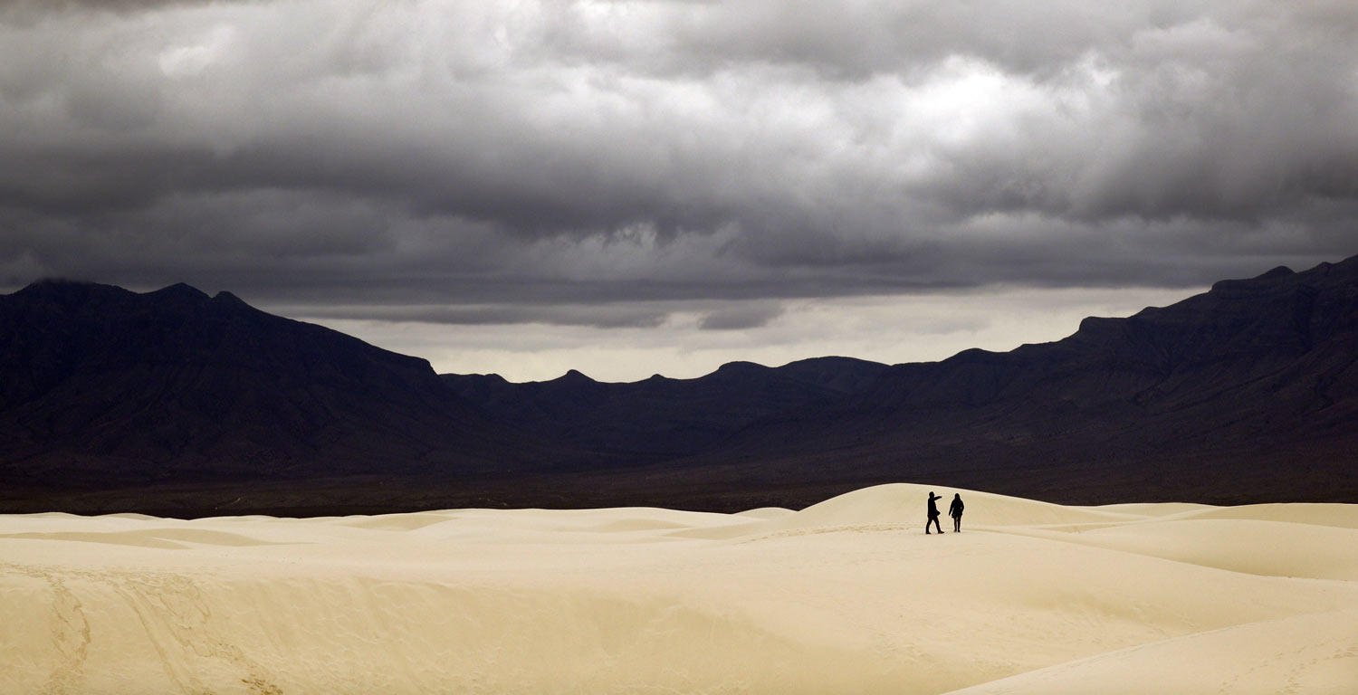 Visitors walk across dunes at White Sands National Monument as a rain storm passes, Sunday, Feb. 10, 2019, near Alamogordo, N.M. (AP Photo/Eric Gay)