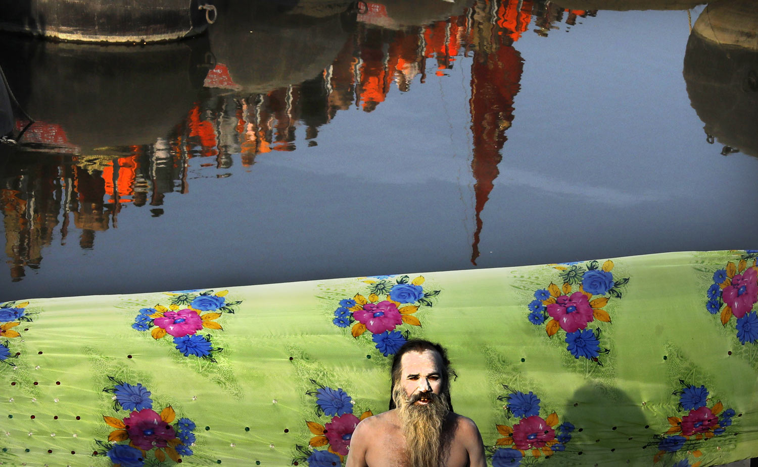 A naked Hindu holy man prays as others cross a pontoon bridge to take ritualistic dip on the auspicious day of Basant Panchami at Sangam, the confluence of sacred rivers the Yamuna, the Ganges and the mythical Saraswati, during the Kumbh Mela or the Pitcher Festival, in Prayagraj, Uttar Pradesh state, India, Sunday, Feb. 10, 2019. The Kumbh Mela is a series of ritual baths by Hindu sadhus, or holy men, and other pilgrims at Sangam that dates back to at least medieval times. Pilgrims bathe in the river believing it cleanses them of their sins and ends their process of reincarnation. (AP Photo/Rajesh Kumar Singh)