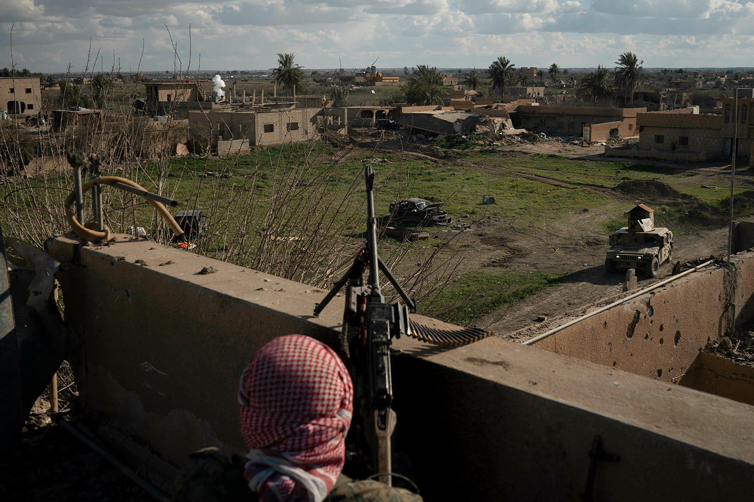 A U.S.-backed Syrian Democratic Forces (SDF) fighter stands atop a building used as a temporary base near the last land still held by Islamic State militants in Baghouz, Syria, Monday, Feb. 18, 2019. (AP Photo/Felipe Dana)