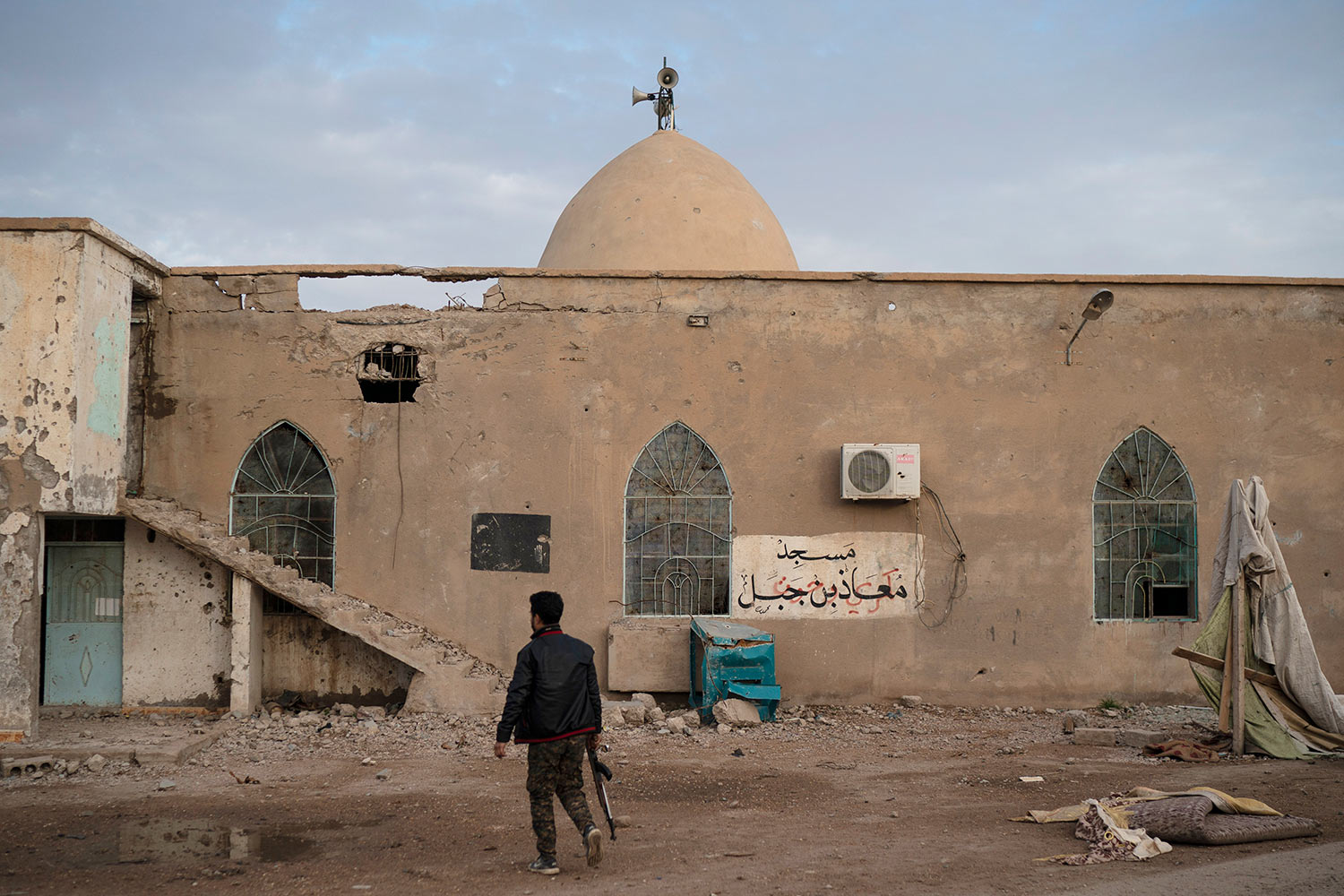A U.S.-backed Syrian Democratic Forces (SDF) fighter walks outside a mosque in a village recently retaken from Islamic State militants near Hajin, Syria, Saturday, Feb. 16, 2019. (AP Photo/Felipe Dana)