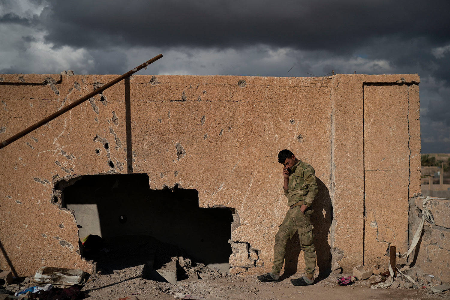 A U.S.-backed Syrian Democratic Forces (SDF) fighter talks on his phone from atop a building recently taken by SDF as fight against Islamic State militants continue in the village of Baghouz, Syria, Sunday, Feb. 17, 2019. (AP Photo/Felipe Dana)
