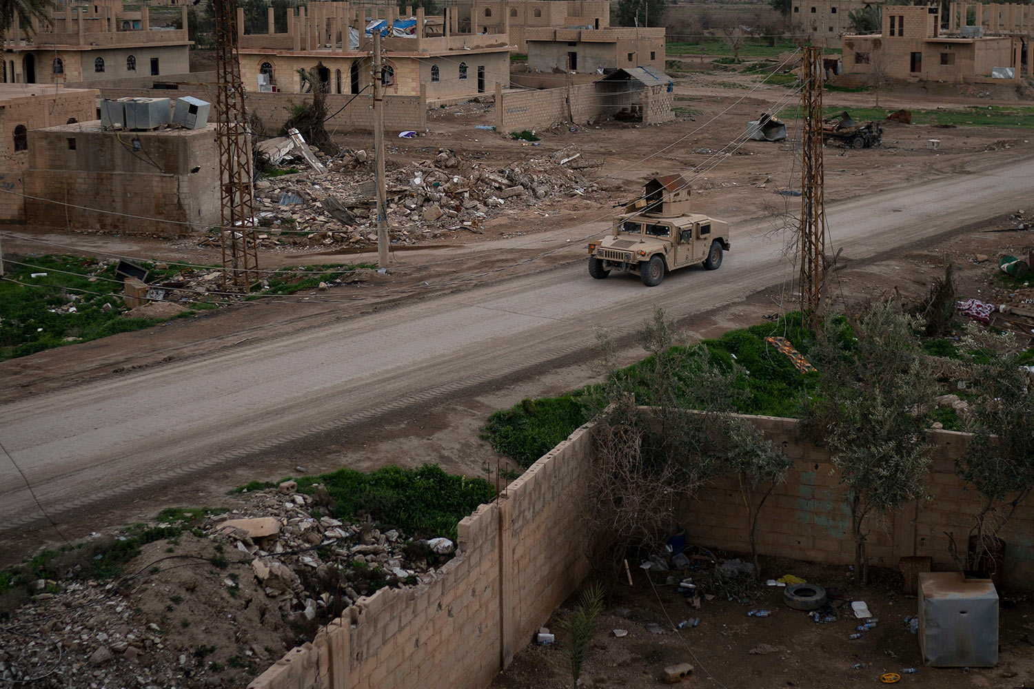 A Humvee drives in a village recently retaken from Islamic State militants by U.S.-backed Syrian Democratic Forces (SDF) near Baghouz, Syria, Sunday, Feb. 17, 2019. Islamic State militants are preventing more than 1,000 civilians from leaving a tiny area still held by the extremist group in a village in eastern Syria, a spokesman for the U.S.-backed Syrian militia fighting the group said Sunday. (AP Photo/Felipe Dana)