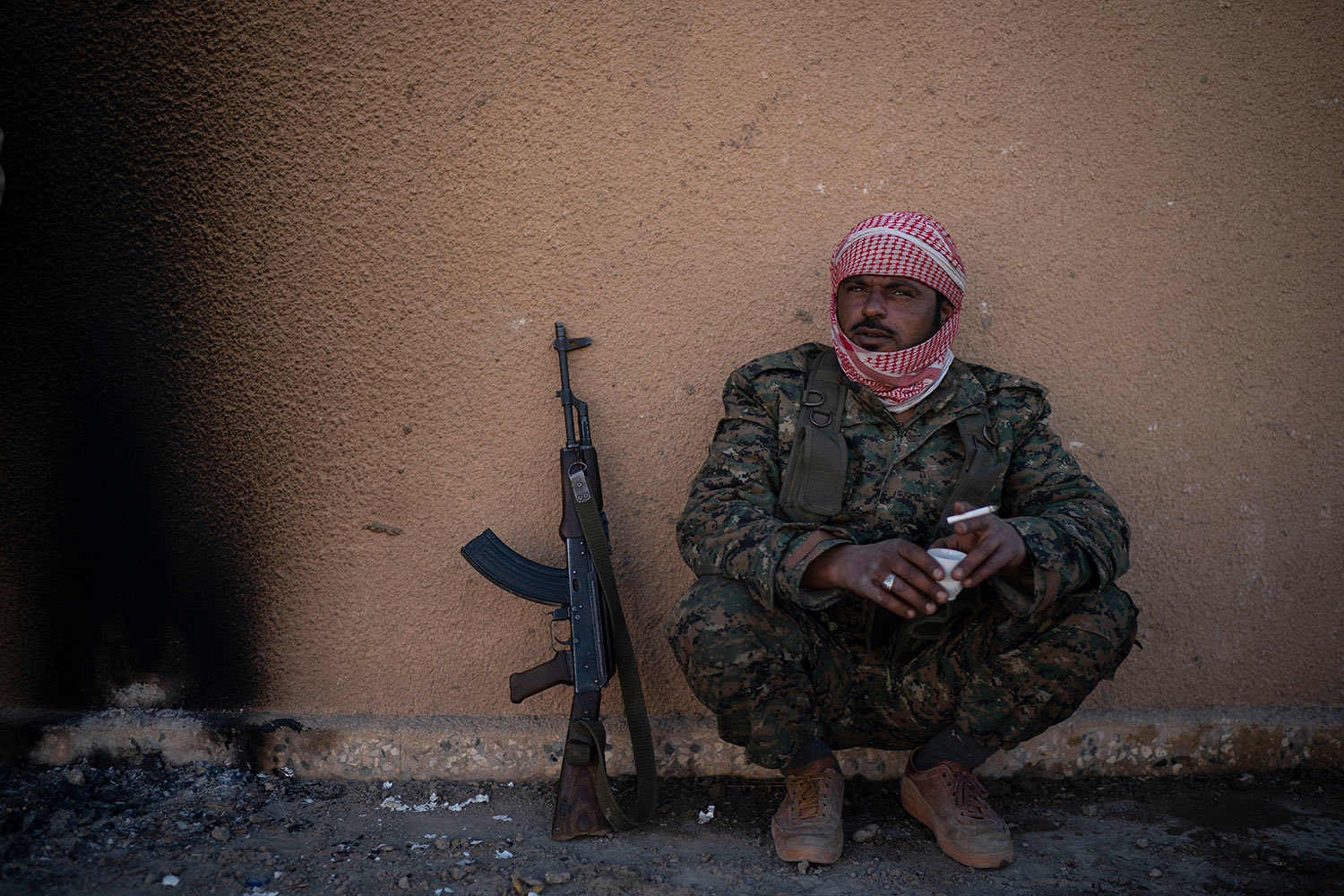 A U.S.-backed Syrian Democratic Forces (SDF) fighter sits inside a building used as a temporary base near the last land still held by Islamic State militants in Baghouz, Syria, Monday, Feb. 18, 2019. (AP Photo/Felipe Dana)