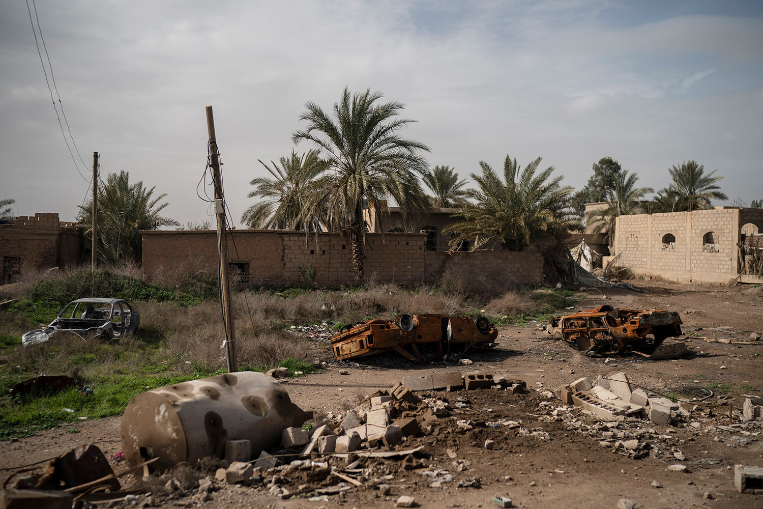 Damaged cars sit in an area recently retaken by U.S.-backed Syrian Democratic Forces (SDF) from Islamic State militants in Susah, Syria, Saturday, Feb. 16, 2019. (AP Photo/Felipe Dana)