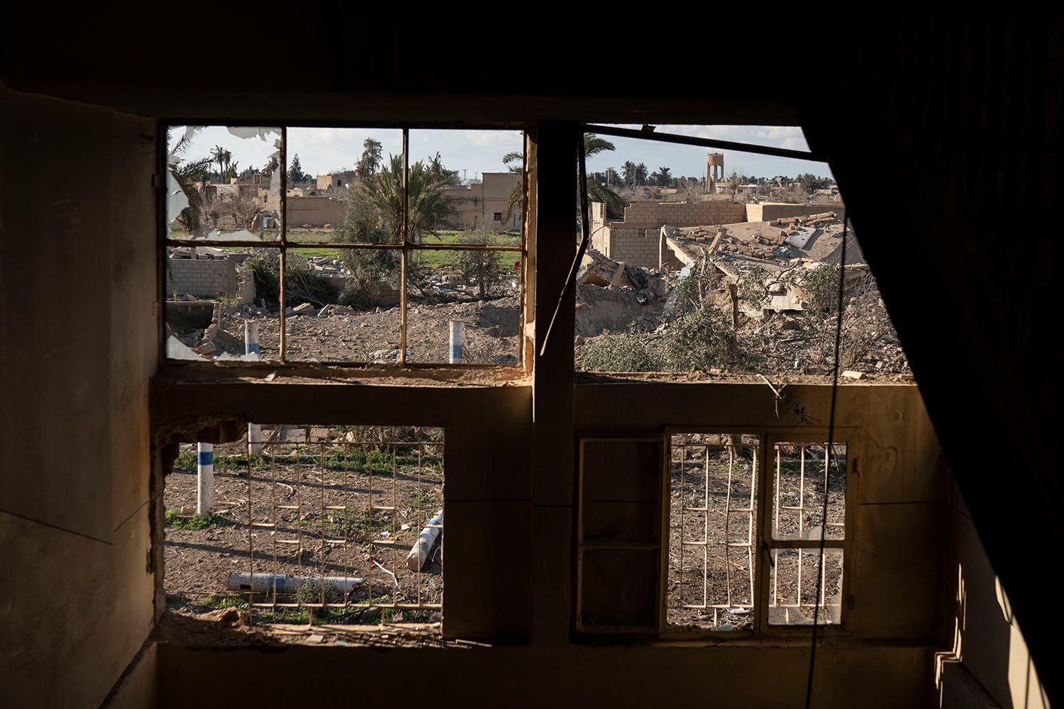 Destroyed homes are framed by damaged windows in a building taken by U.S.-backed Syrian Democratic Forces (SDF) near the last land still held by Islamic State militants in Baghouz, Syria, Monday, Feb. 18, 2019. (AP Photo/Felipe Dana)