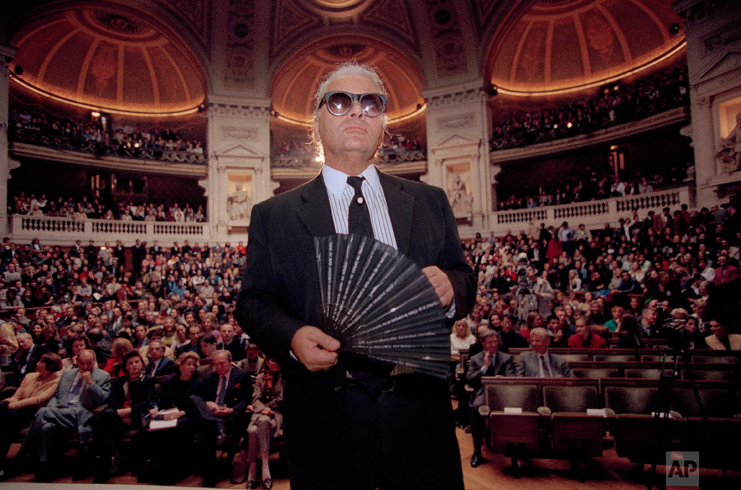 Karl Lagerfeld, the German fashion designer for Chanel, holds his fan as he enters the main auditorium at the Sorbonne, the oldest and most famous university in France, Oct. 18, 1994. (AP Photo/Lionel Cironneau)
