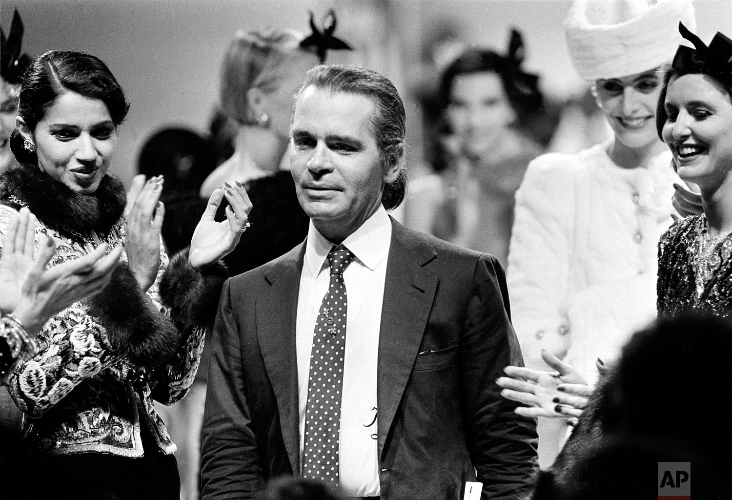 German fashion designer Karl Lagerfeld is applauded by his models at the end of the presentation of Chanel's fall and winter haute couture collection in Paris, France, July 26, 1983. (AP Photo/Jacques Langevin)