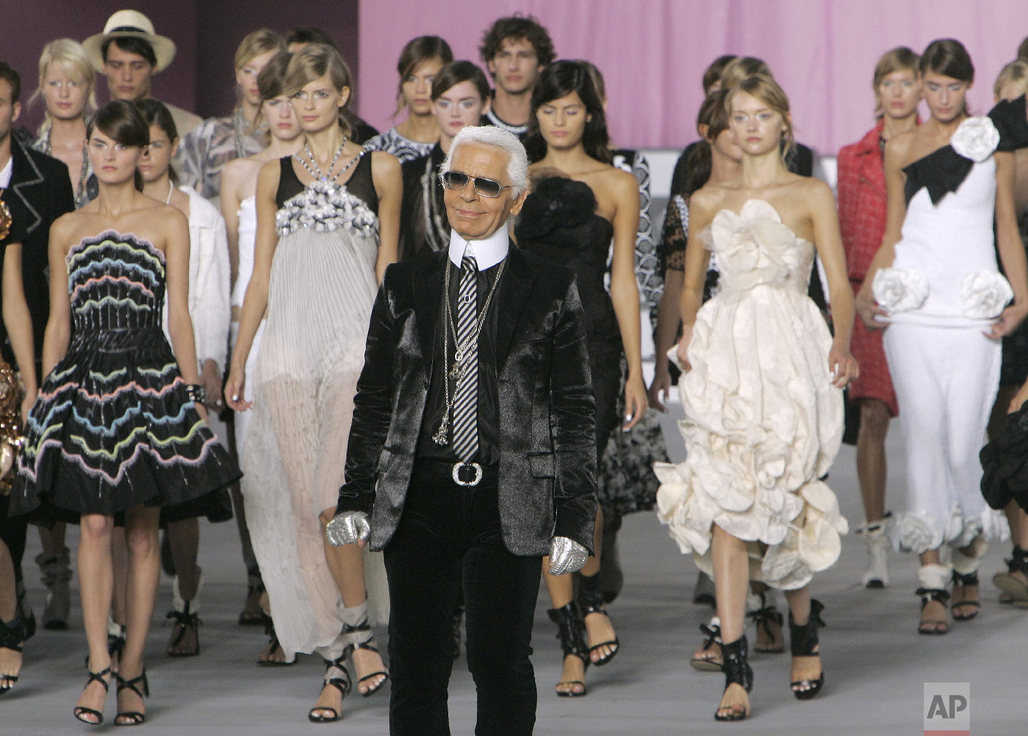 German fashion designer Karl Lagerfeld acknowledges applause from the public during the presentation of his Spring/Summer ready to wear 2006 collection for Chanel, in Paris, Oct. 7, 2005. (AP Photo/Michel Euler)