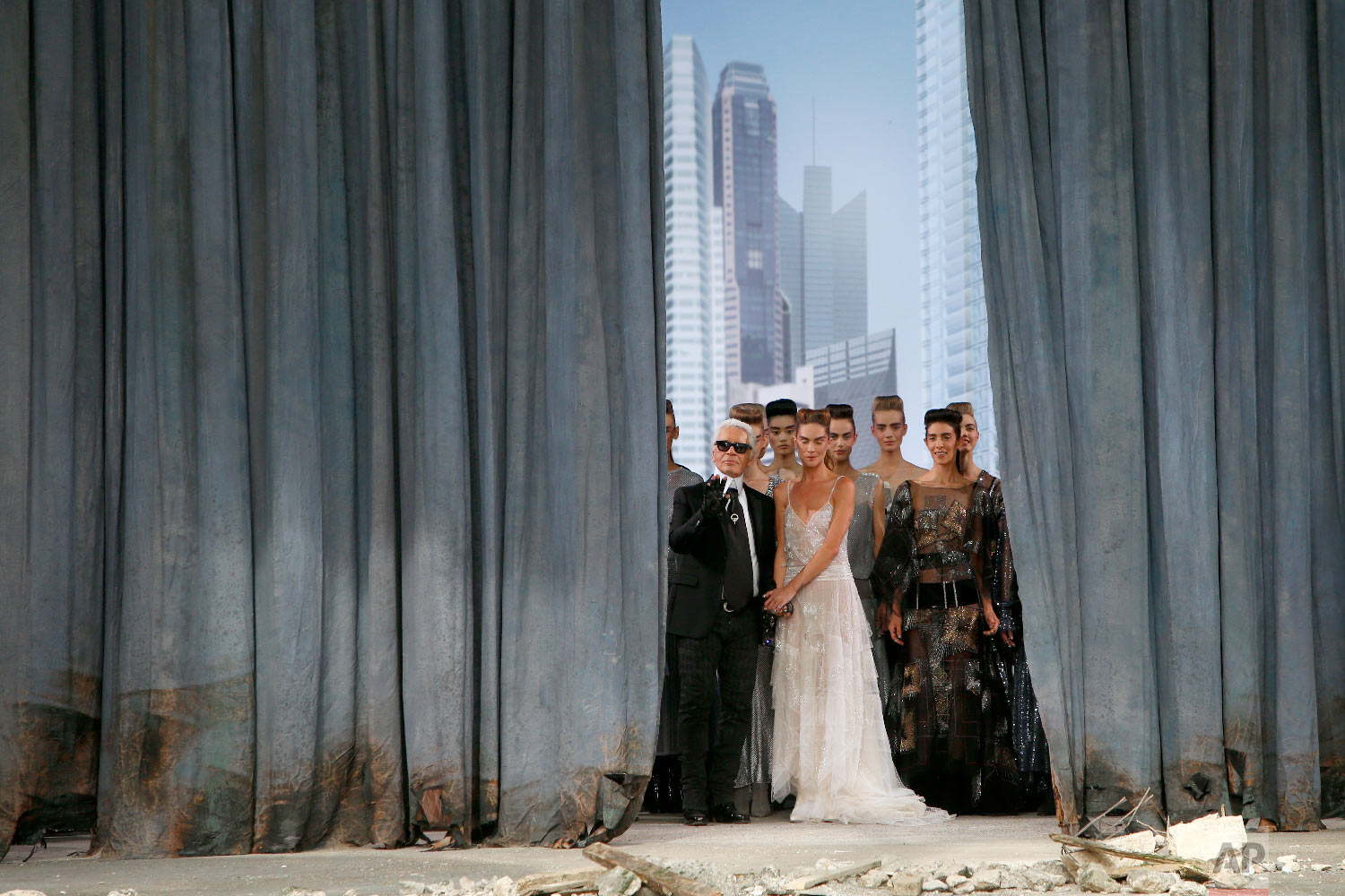 German fashion designer Karl Lagerfeld, foreground left, stands with models on stage as he acknowledges applause following the presentation of the Haute Couture Fall-Winter 2013-2014 collection he designed for Chanel, July 2, 2013 in Paris. (AP Photo/Francois Mori)