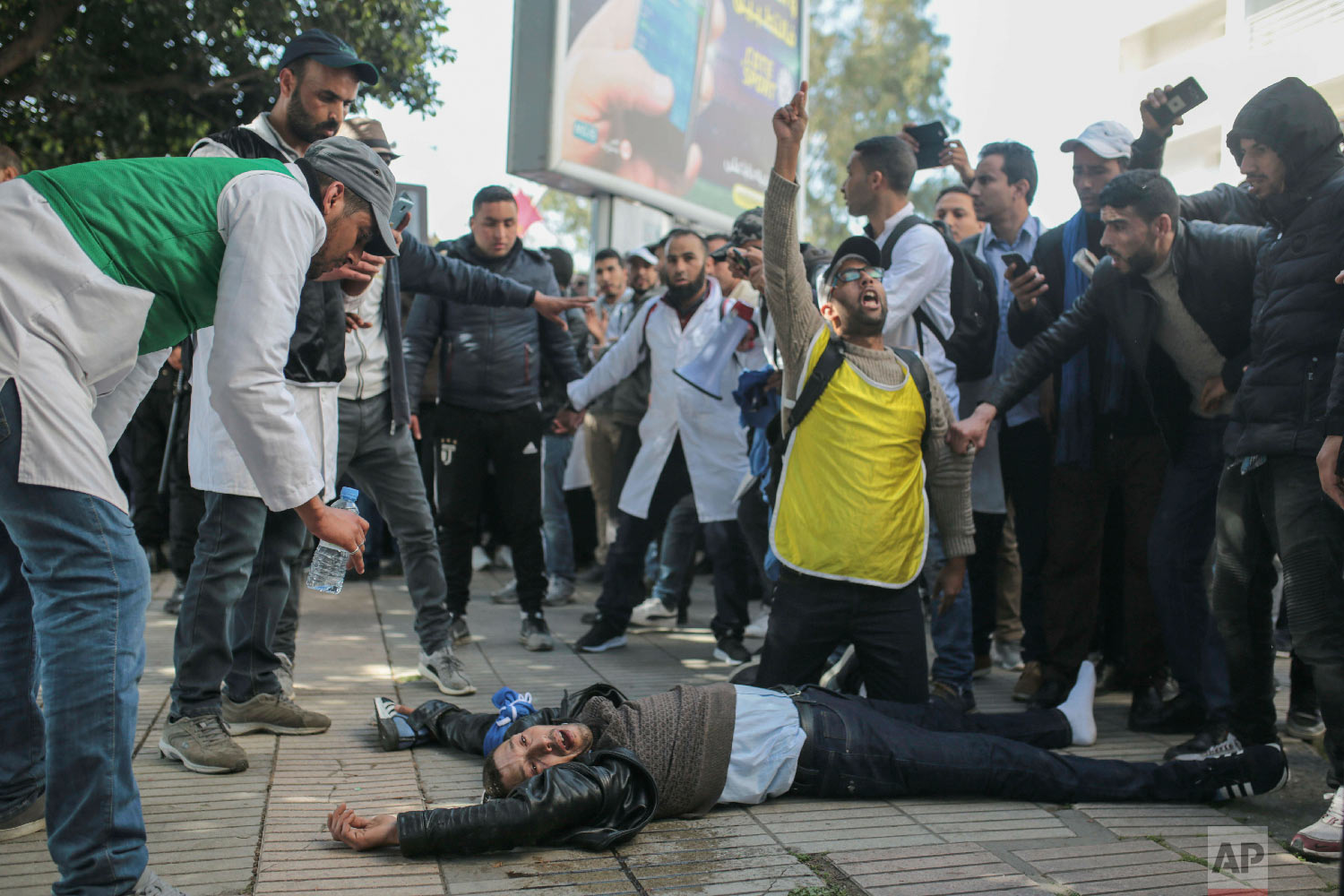 An injured protesting teacher is tended to by fellow protesters after security forces used water cannons and batons to disperse a demonstration in Rabat, Morocco, Feb. 20, 2019. (AP Photo/Mosa'ab Elshamy)