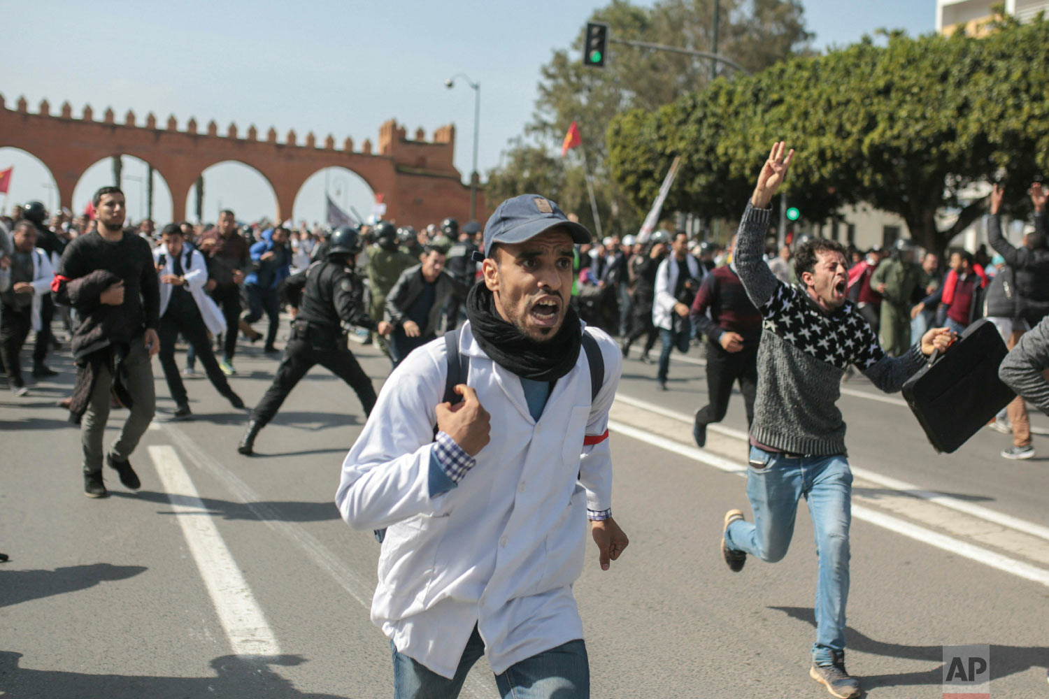 Protesting teachers run from security forces attempting to disperse a demonstration in Rabat, Morocco, Feb. 20, 2019. (AP Photo/Mosa'ab Elshamy)