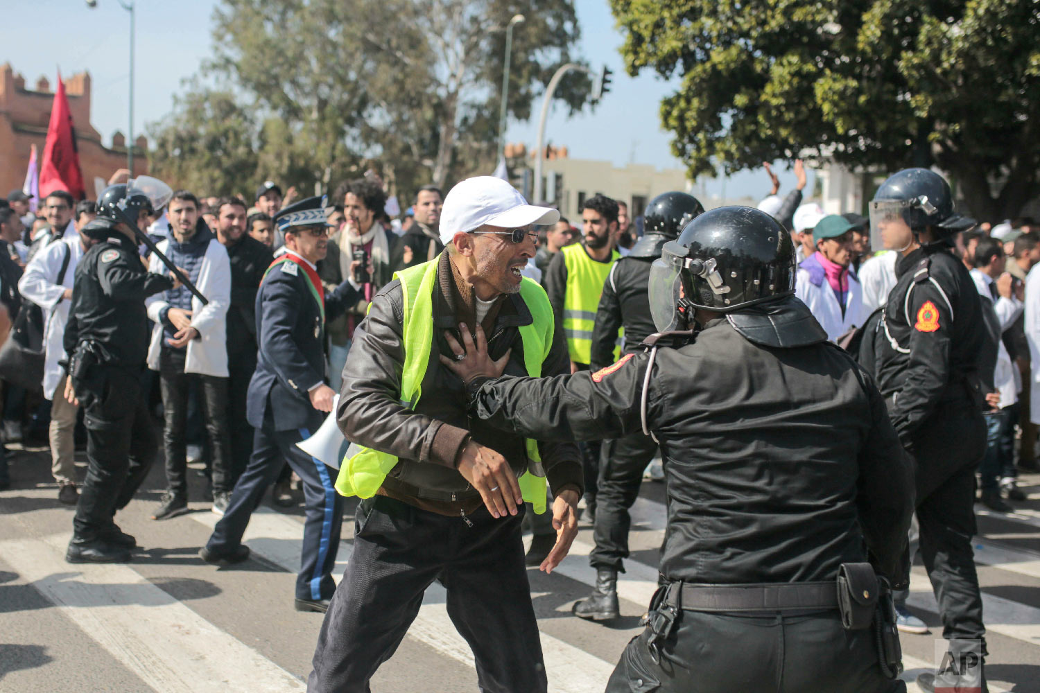 A teacher wearing a yellow vest is confronted by security forces during a demonstration in Rabat, Morocco, Feb. 20, 2019. (AP Photo/Mosa'ab Elshamy)