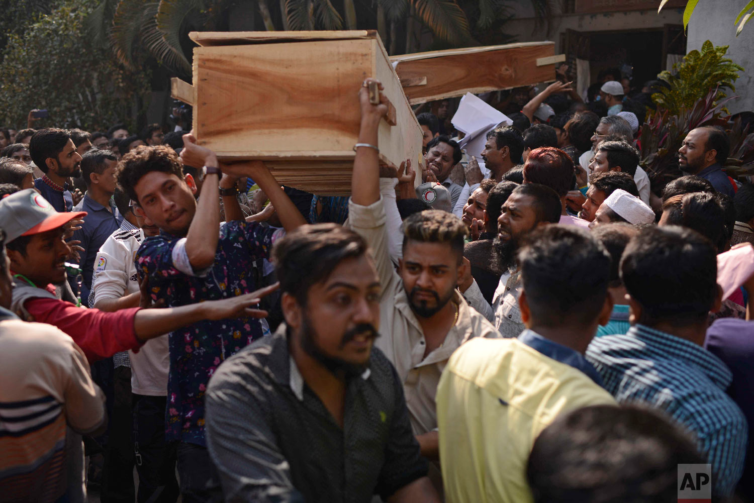 Bangladeshis carry coffins of relatives out from a morgue after they were killed in a fire in Dhaka, Bangladesh, Thursday, Feb. 21, 2019. (AP Photo/Mahmud Hossain Opu)