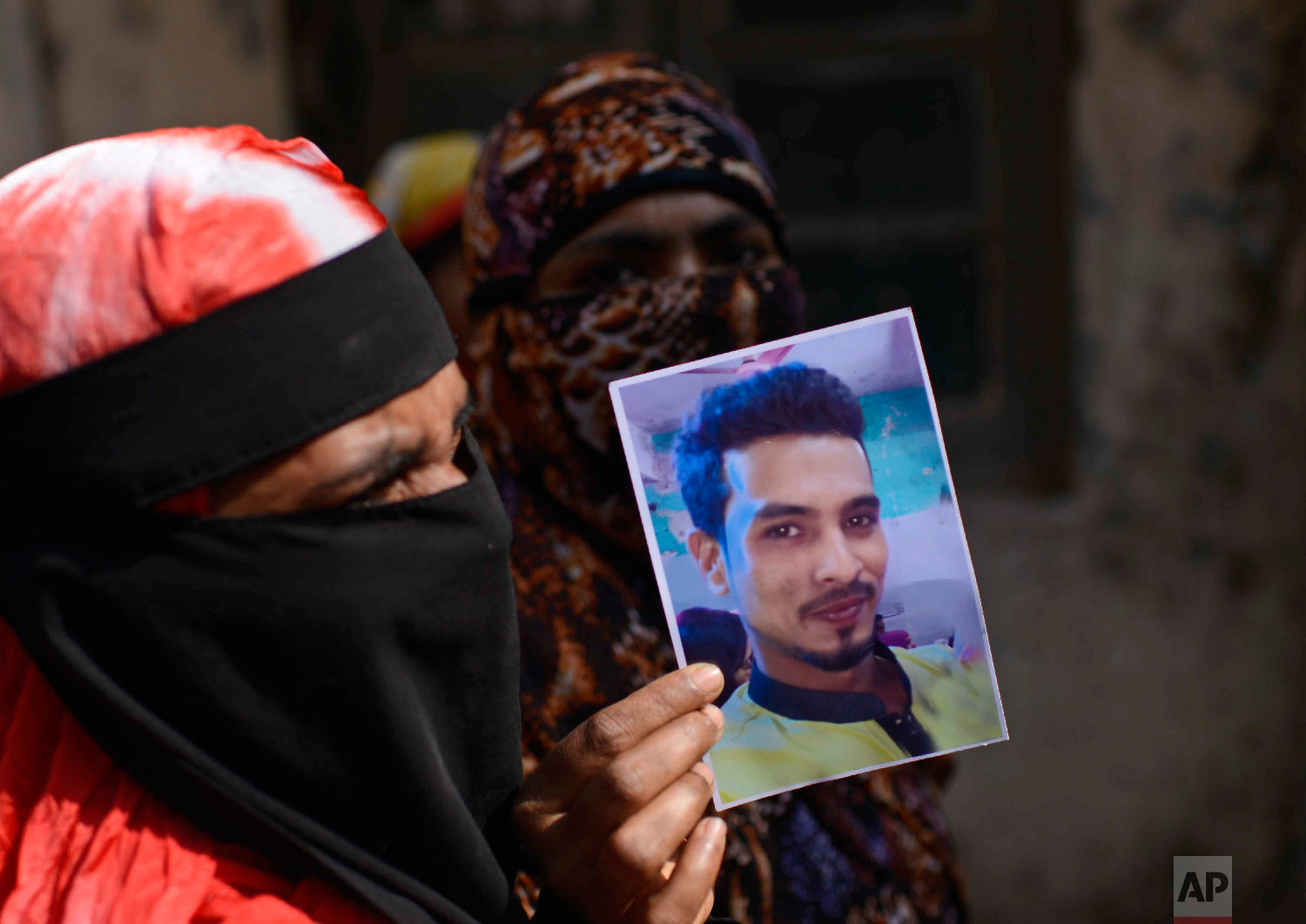 A woman displays a photograph of a relative who died in a fire, outside a morgue in Dhaka, Bangladesh, Thursday, Feb. 21, 2019. (AP Photo/Mahmud Hossain Opu)
