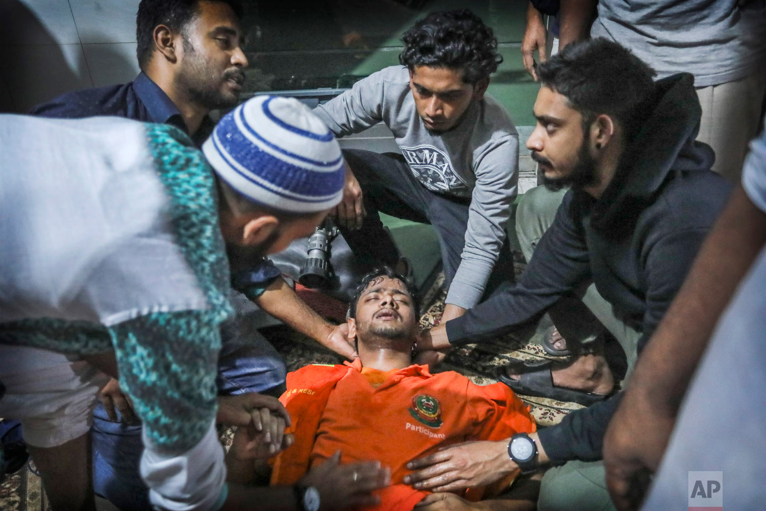 Locals help a Bangladeshi firefighter who lost consciousness briefly while trying to douse flames of a smoldering fire in a building in Dhaka, Bangladesh, Thursday, Feb. 21, 2019. (AP Photo/Zabed Hasnain Chowdhury)