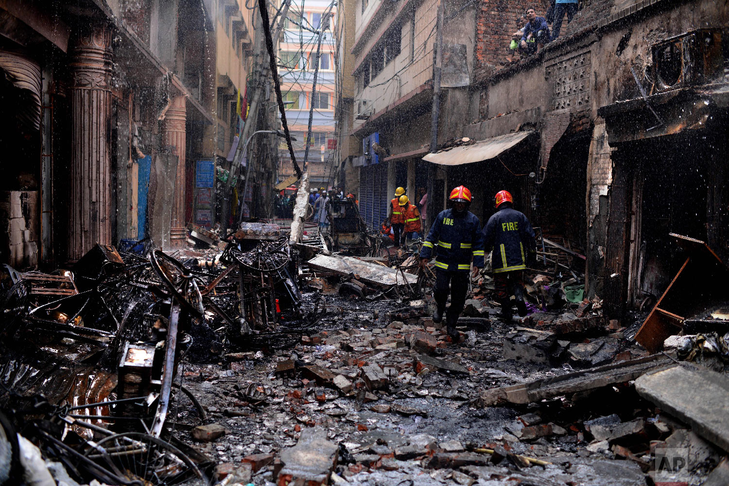 Firefighters gather around buildings that caught fire late Wednesday night in Dhaka, Bangladesh, Thursday, Feb. 21, 2019. (AP Photo/Mahmud Hossain Opu)